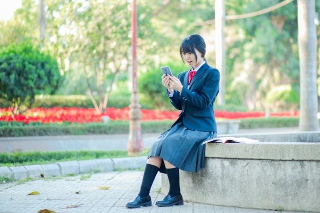 スマホを見る女子高生